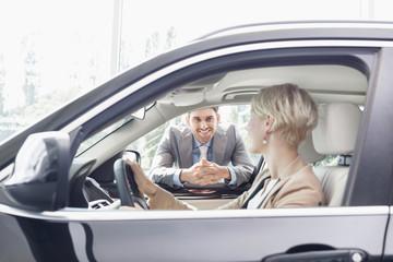 Autohändler mit Kunden sitzen im neuen Auto