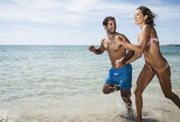 Spanien, Paar am Strand laufen