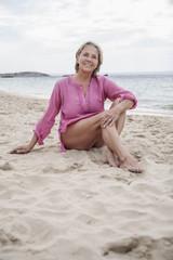 Spanien, Seniorin sitzt am Strand