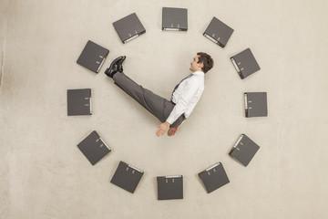 Geschäftsmann im Kreis der Aktenordner bilden Uhr