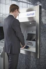 Deutschland, Köln, Mann am Geldausgabemaschine am Flughafen