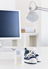 Schreibtisch mit Babyflasche und Babyschuhe