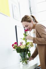 Deutschland, München, junge Frau riecht Blume