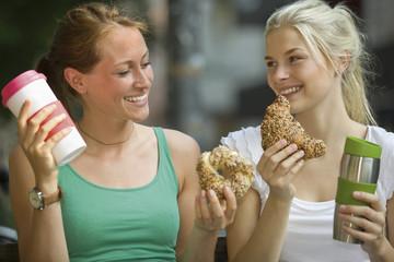 Deutschland, Köln, Junge Frauen mit Kaffee und Croissants