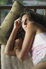 Indonesien, Junge Frau entspannt auf der Veranda