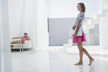 Spanien, Paar mit Laptop in der modernen Wohnung