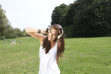 Deutschland, Berlin, junge Frau hört Musik im Treptower Park