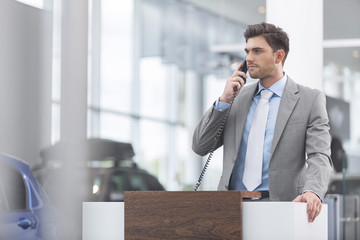 Autohändler am Telefon im Showroom