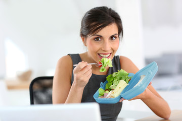 Busy businesswoman having lunch in office