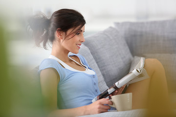 Brunette woman reading magazine at home in nightwear