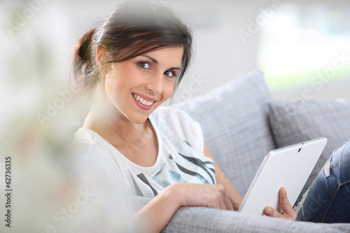 Brunette girl at home connected on tablet