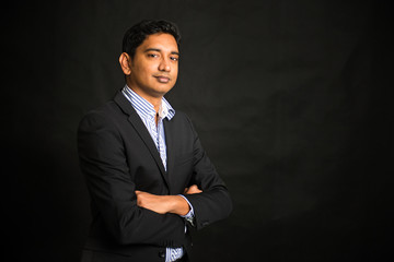 indian business man on dark background, crossed arm