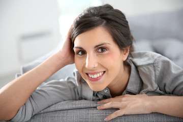 Attractive young woman sitting in sofa