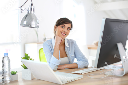 Smiling office worker sitting at desk