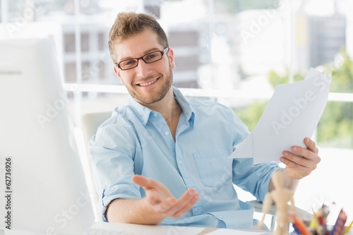 Happy designer sitting at his desk gesturing at camera
