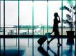 Leinwanddruck Bild - Business woman at Airport - Silhouette of a passenger