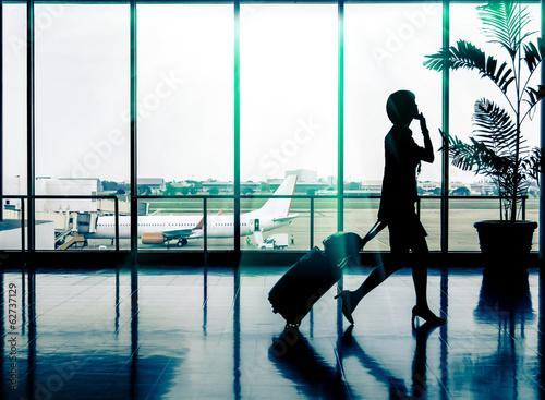 Leinwanddruck Bild Business woman at Airport - Silhouette of a passenger