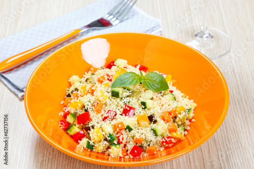 Couscous with vegetables in orange dish