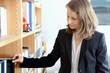 Frau nimmt Buch aus Regal