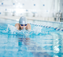 Young girl in goggles swimming breaststroke stroke style