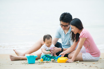 asian family enjoying quality time on the beach with father, mot