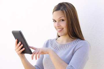 Beautiful woman holding a tablet reader and looking at camera