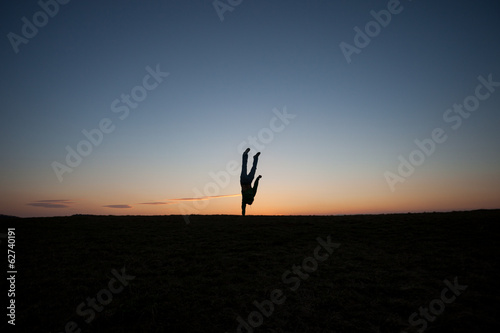 one handed handstand in sunset