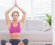 Fit blonde meditating in lotus pose with arms raised