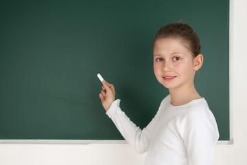 Schülerin steht an Tafel und schreibt