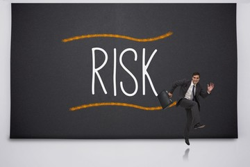 Happy businessman jumping against the word risk