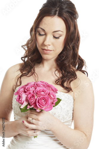 Female bride holding a wedding bouquet of pink roses thoughtful