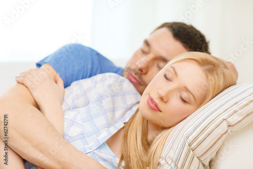 smiling happy couple sleeping at home