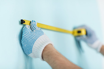 closeup of male in gloves measuring wall with tape