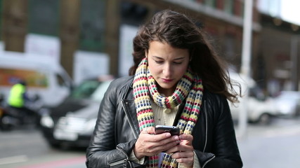 Attractive young woman using a smart phone and looking around