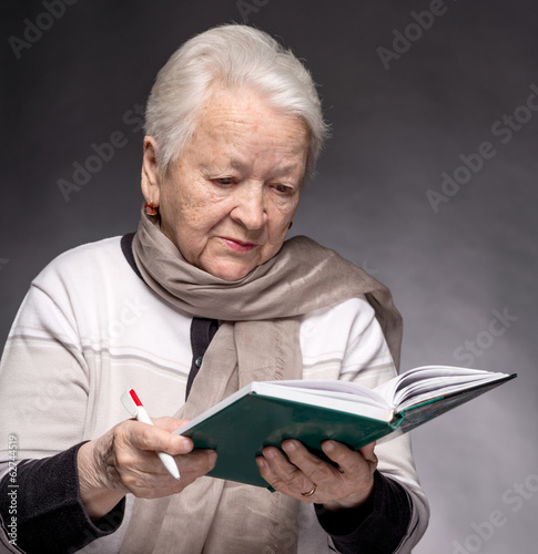 Senior woman writing notes in a notebook