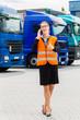 Spediteurin vor Lastwagen und LKW auf Depot