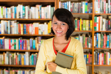 Girl in library holding a book
