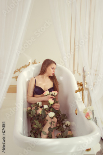 Girl lying in the bathroom with roses