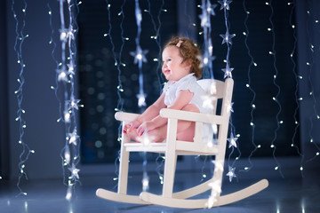 Beautiful little toddler girl with curly hair wearing a white dr