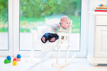 Funny newborn baby boy relaxing in a white rocking chair