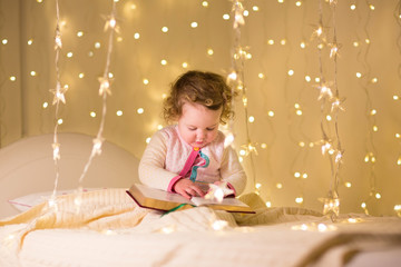 Cute little toddler girl reading a book in a dark room