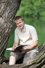 The young man with the book in park on the bank of lake