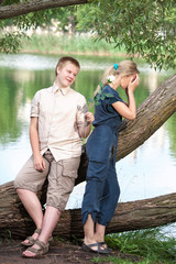 Young guy and girl on nature,reconciliation after quarrel..