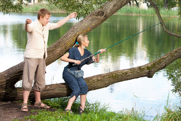 Young people on fishing.The guy shows the size of fish