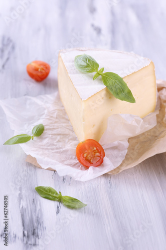 Tasty Camembert cheese with basil and tomato, on wooden table