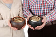Two ceramic pots with golden coins in male and female hands,