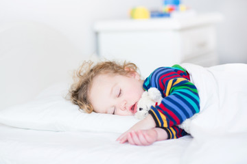 Adorable toddler girl taking a nap in a white bed