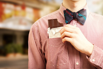 Closeup photo of man taking chocolate out of pocket at street