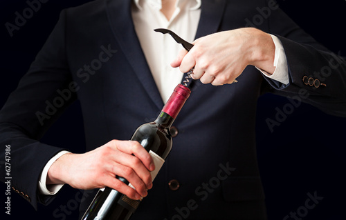 Closeup photo of man opening bottle of wine with corkscrew
