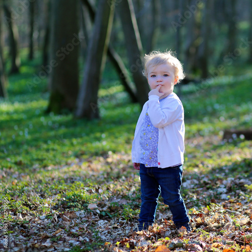 Funny  toddler girl in casual clothes playing in spring forest